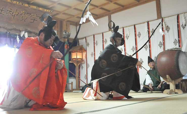 太々神楽を舞う神職。弓矢で邪神を射る動きを舞で表現した