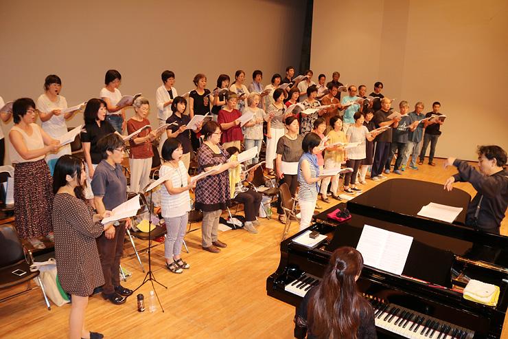 山下さん(右)の指導で練習に励む団員=大山文化会館