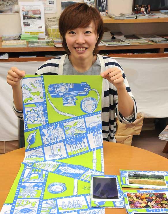 木曽地方の風景や祭りなどを描いた手拭いを持つ加藤さん