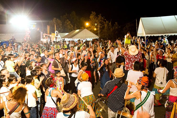 屋外ステージ周辺で盛り上がる聴衆。県外からの来場も目立つ=2015年8月、南砺市園芸植物園