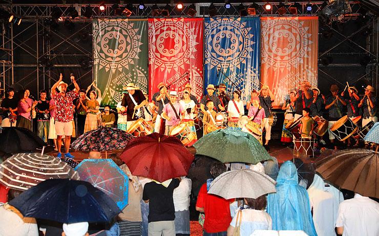雨の中、大勢の観客を前に熱気あふれる演奏を披露する「トゥーマラッカ」と「なんとジュニアコーラス♪」のステージ=南砺市園芸植物園