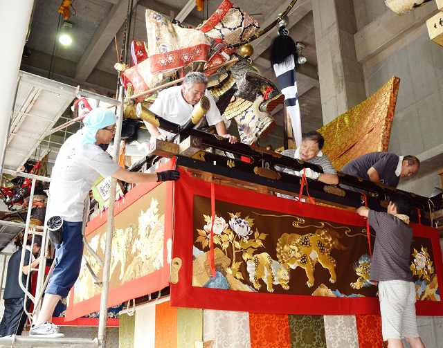 敦賀まつりに向けて山車に水引幕を取り付ける住民=28日、福井県敦賀市相生町のみなとつるが山車会館