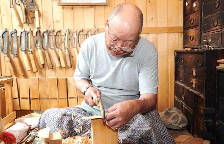 細かい手作業を重ねて「お六櫛」を作る篠原武さん。後ろに並ぶ道具も手作りだ