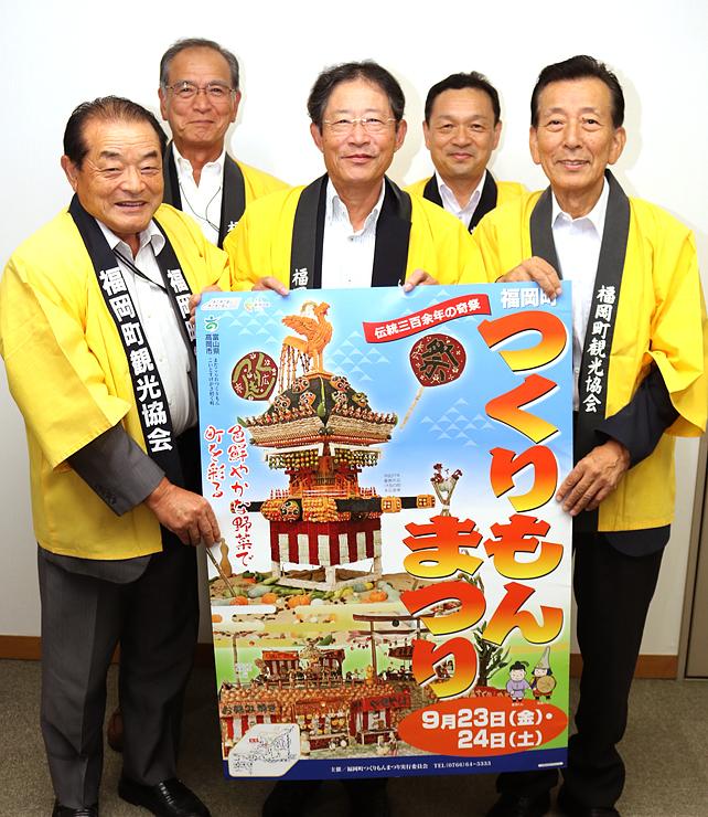 ポスターを手にする(前列左から)山崎事務局長、上田実行委員長、大野実行本部長と(後列左から)吉田事業部長、小崎課長=北日本新聞高岡支社