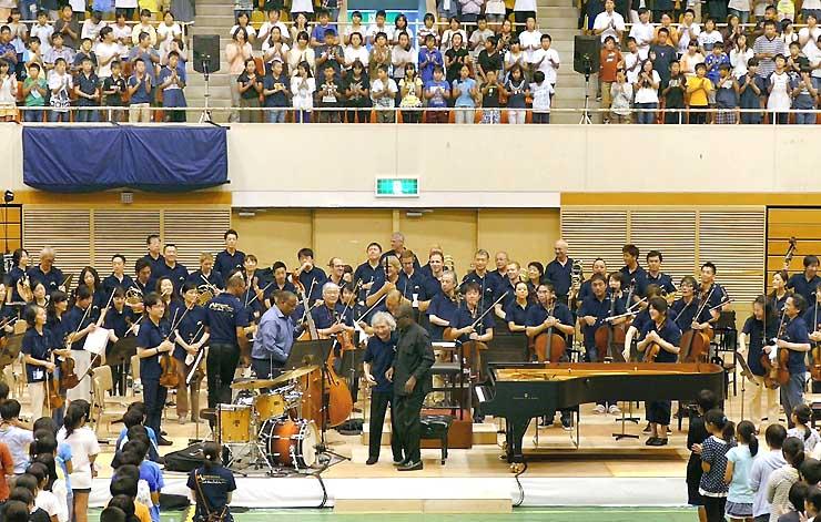 「故郷」の大合唱を締めくくり、会場全体の拍手に応える小澤さん(中央)とロバーツさん(右隣)=31日、松本市総合体育館