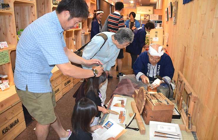 「お六櫛」作りを披露する北川さんの手元を熱心に見つめる来店者ら