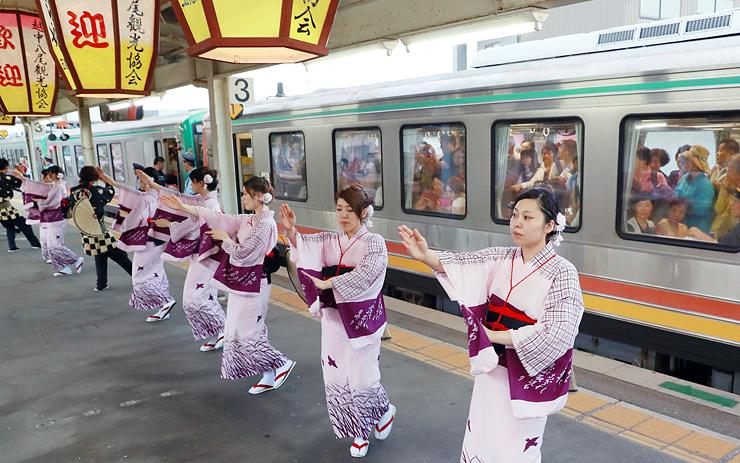始発列車の乗客に見送りおわらを披露する福島の踊り手=JR越中八尾駅