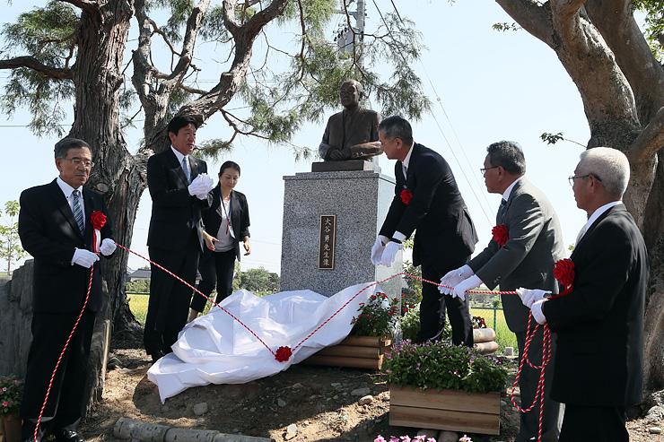 大谷勇さんの胸像を除幕する長島自治会長(右)や桜井市長(左から2人目)ら=小矢部市水落