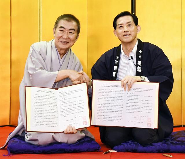 協定書を取り交わし、握手する松崎市長(右)と桂会長=3日、大阪市の生國魂神社(小浜市提供)