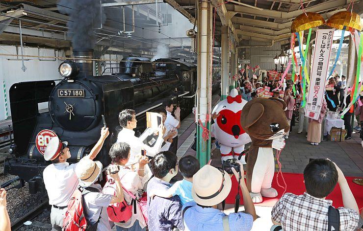 くす玉を割り、SLばんえつ物語号の乗車80万人を祝った記念行事=3日午前、新潟市中央区のJR新潟駅
