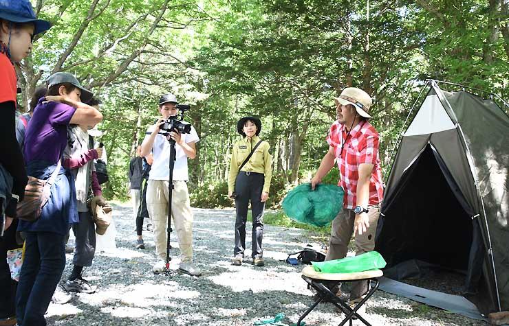 参加者に携帯トイレの使用方法を説明する戸隠登山ガイド組合の秦孝之さん(右)