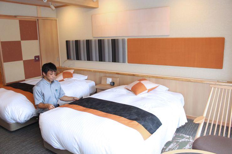ベッドやクッションカバー、壁面の装飾に伝統織物が使われた客室=湯沢町湯沢