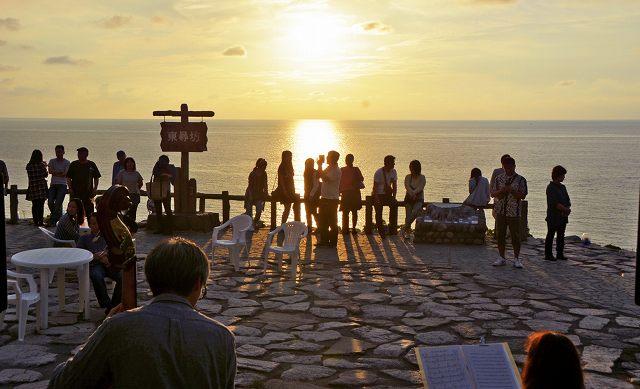 2015年9月に行われた「東尋坊夕陽ハートカクテル」でジャズの演奏を楽しみながら夕日を眺める観光客ら=福井県坂井市の東尋坊