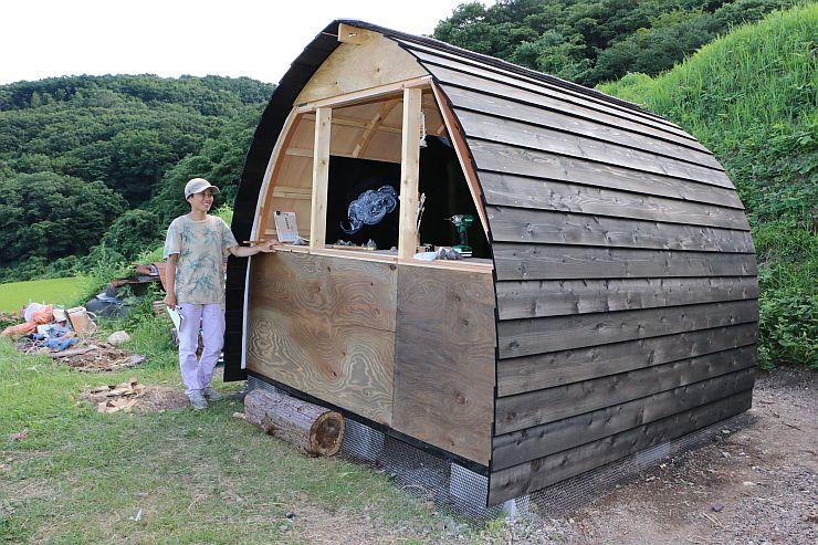 棚田の中に世阿弥の書斎をイメージして建てた小屋を眺める寺田佳央さん=佐渡市岩首