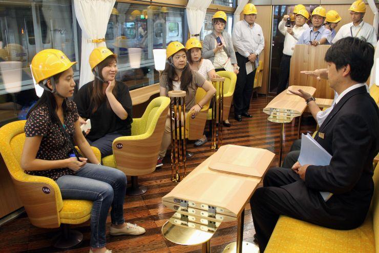 リゾート列車内で説明を受ける台湾の旅行代理店と経済誌の担当者(左の4人)=7日、上越市
