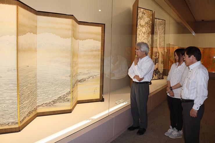立山連峰を背景に富山湾を描いたびょうぶ(左)など石崎作品が並ぶコーナー