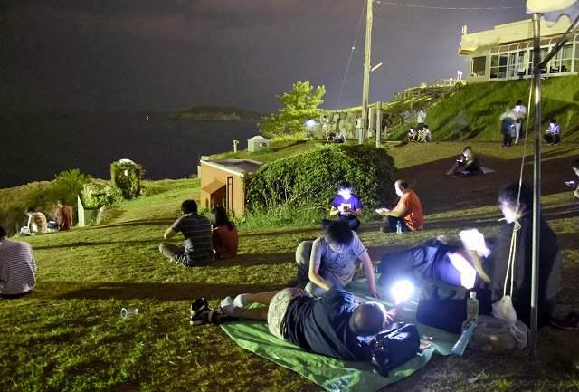 ポケストップが多く集まる東尋坊では夜が更けても多くの人がゲームに興じている=7日、福井県坂井市