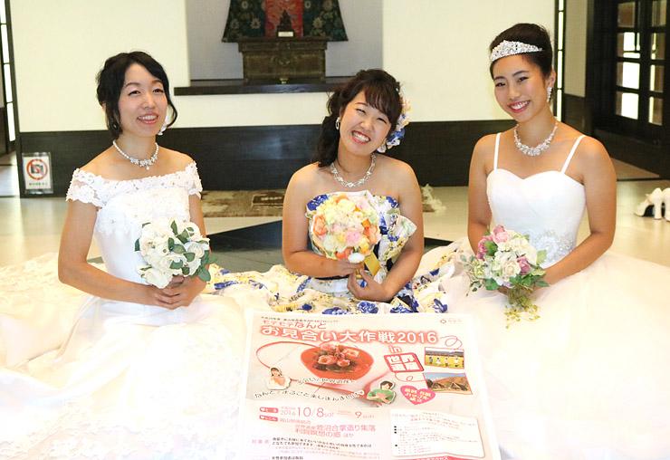 花嫁衣装でポスター(中央手前)を掲げ、お見合いイベントをPRする地域おこし協力隊員
