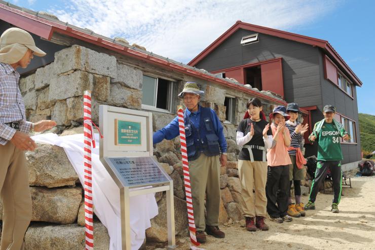 参加者が歩荷リレーで運び、西駒山荘の石室前に設置された国登録有形文化財の登録プレート=10日午後1時