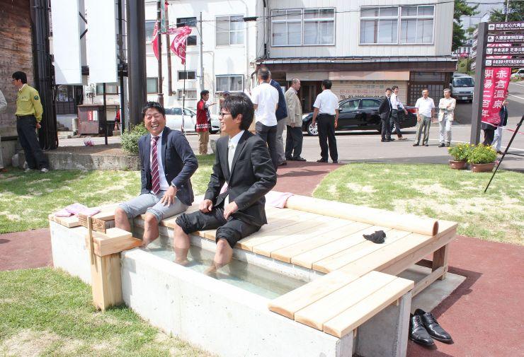 赤倉開湯200年を記念して完成した足湯を楽しむ人たち=10日、妙高市