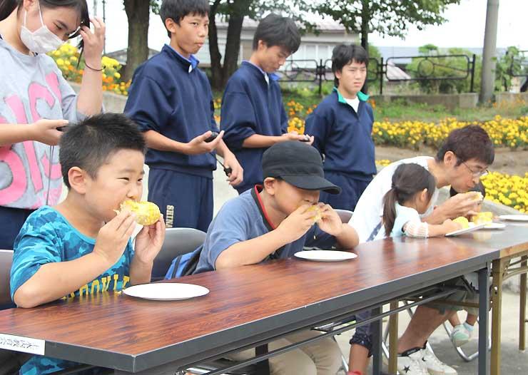 信濃町特産トウモロコシを頬張る早食い大会の参加者たち=信濃町の黒姫駅前