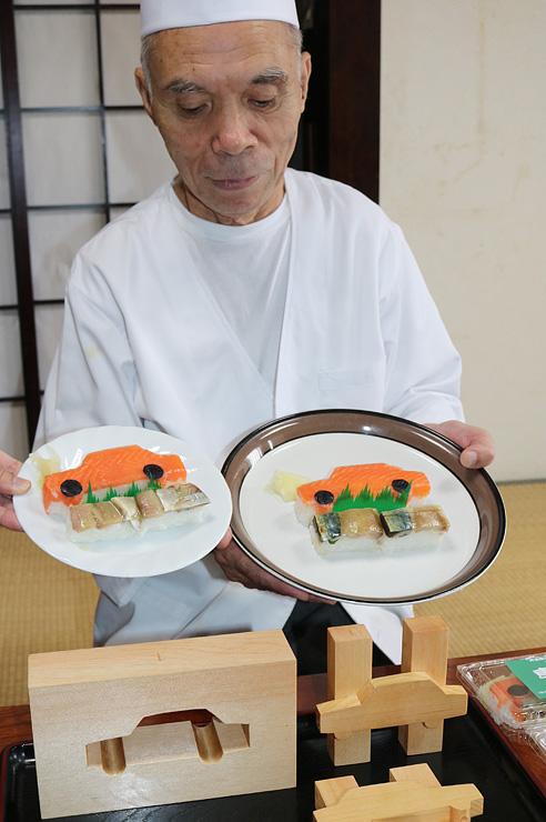 型枠を並べ、車ヶ寿司を手にする吉江店主=南砺市井波の福寿し