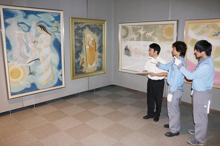 「密林を行く玄奘法師」や「レダと白鳥」などを展示する加治学芸員(右から3人目)