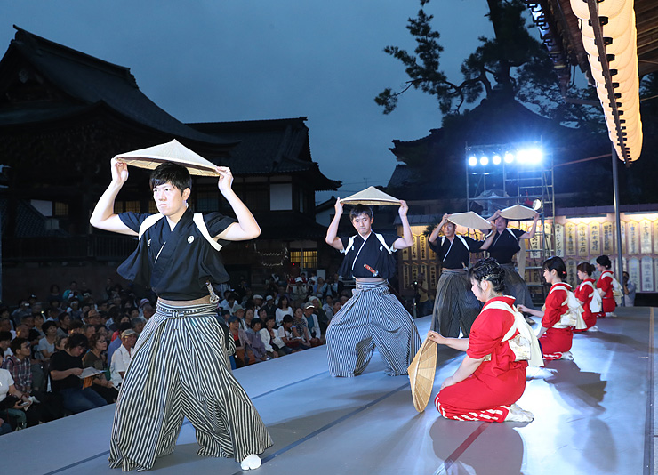 修復をほぼ終えた本堂に設けられた特設ステージで麦屋節を披露する西下町の踊り手=城端別院善徳寺