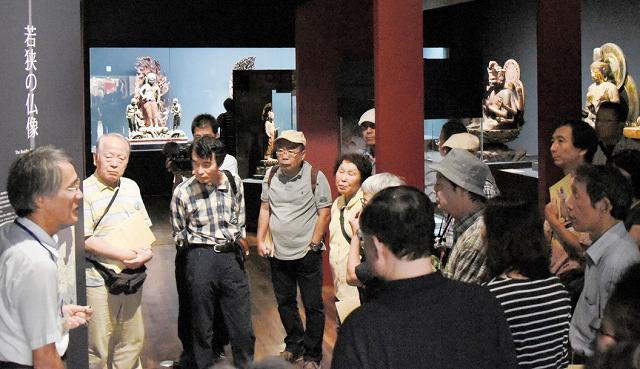 小浜の歴史の紹介に耳を傾ける秘仏めぐりツアーの参加者=17日、福井県立若狭歴史博物館