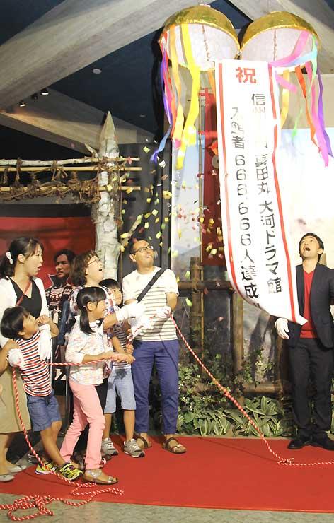 66万6666人目の入館者となり、くす玉を割る永田さん一家(左)と大野さん