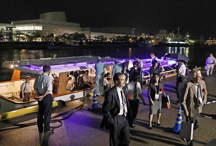 信濃川ウォーターシャトルから降りて懇親会場のピア万代に向かう参加者ら=新潟市中央区
