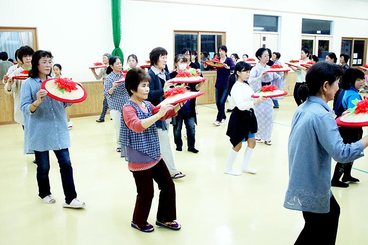菅笠を手に踊りの練習をする住民ら=福岡さくら会館