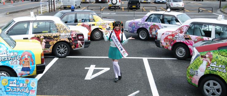 ナミキちゃんの衣装でPRする高木さんと6台の「痛タク」=21日、飯田市