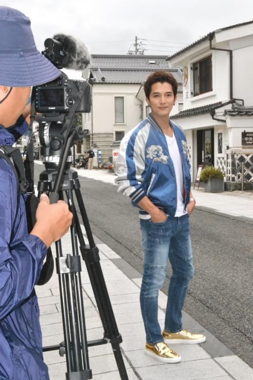 中心市街地の中町通りで旅番組の収録をするロイ・チウさん=21日、松本市