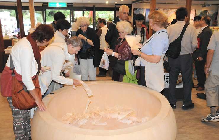 プレオープンした「ねざめ亭」に展示されたヒノキの浴槽を見る外国人観光客ら