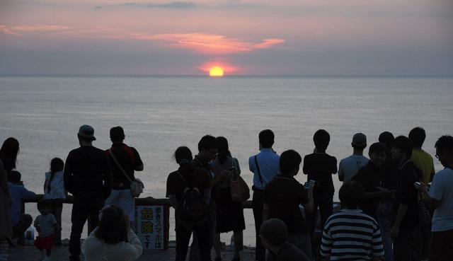 ライブ演奏が流れる中、沈む夕日を眺めるカップルや家族連れ=24日、福井県坂井市の東尋坊