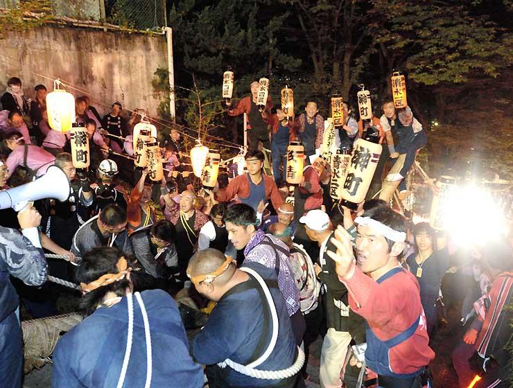 ちょうちんを手に200段の石段を御柱と共に上る氏子たち=25日、諏訪市上諏訪の手長神社