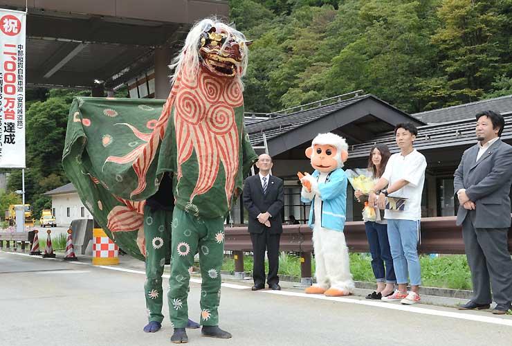 記念に披露された平湯温泉の伝統芸能を見る安房峠道路の2000万台目のドライバーら