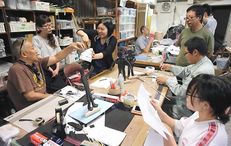 沢さん(左)の指導を受けながら新しい人形の制作を進める参加者たち=飯田市