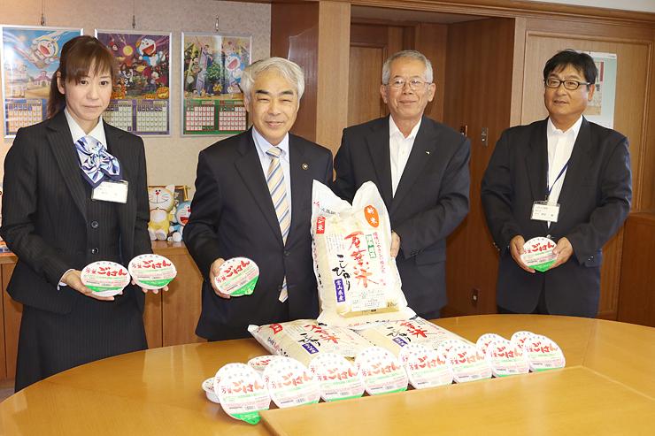 高橋市長(左から2人目)にパックご飯などを贈った萩原組合長(同3人目)=高岡市役所