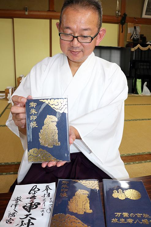 初めて作ったオリジナルの御朱印帳を持つ大伴宮司=放生津八幡宮