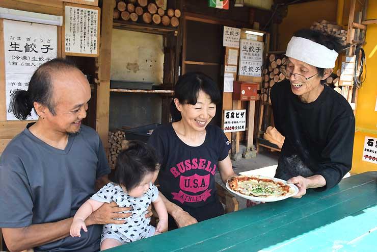 客に手作りピザを提供する小師さん(右)