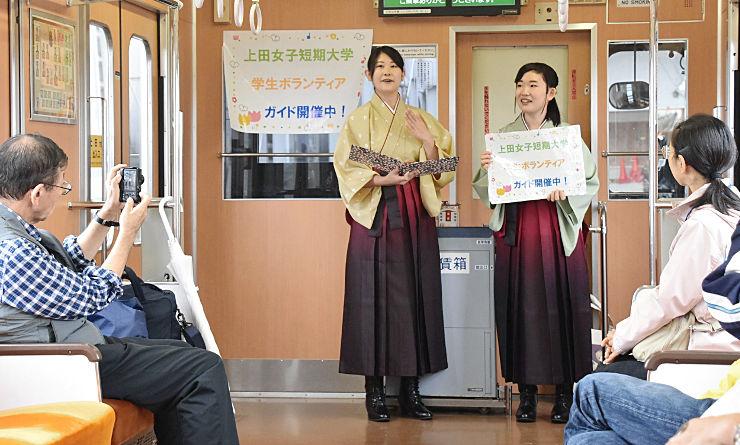 別所温泉行きの列車に乗った観光客らに沿線を紹介する学生ガイド