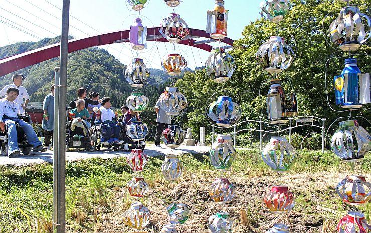 秋の里山に映える「カラフル風車」。作った障害者らも満足そうに眺めた=1日、阿賀町豊実