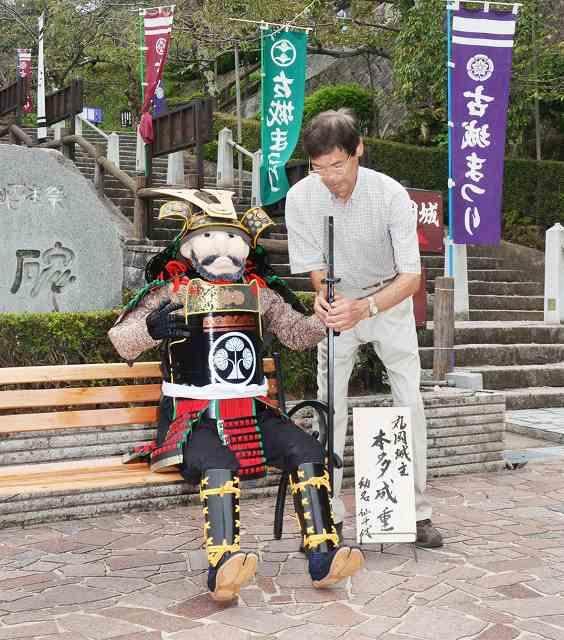 丸岡城天守のふもとに本多成重のかかしを設置する岡上さん=3日、福井県坂井市