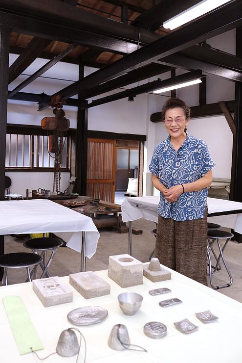 修復した鋳物工場を案内する神初良子さん。手前は鋳物体験で製作できるスズ製品