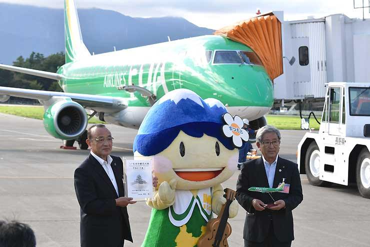 松本市観光大使に新たに任命されたFDA11号機の前で行われた引き継ぎ式=6日、県営松本空港