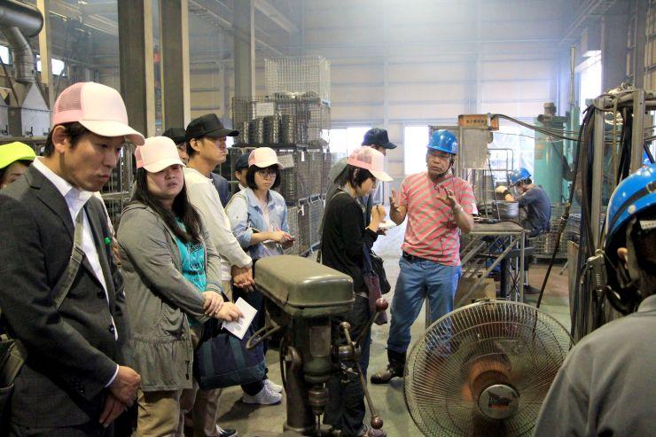 製造工程についての説明を聞く見学者=6日、三条市の三条特殊鋳工所