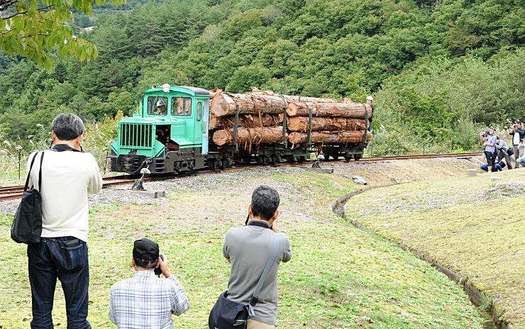 デモ走行する運材列車を写真に収める愛好者たち