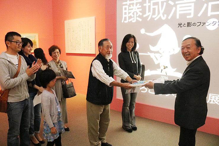 雪山館長(右)から記念品を受け取る林さん(中央)と、前後の来場者となった車谷さん(手前左)と福田さん(右から2人目)